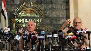 Egyptian General Mamduh Shahin (R) and General Mohammed al-Assar, members of the Supreme Council of the Armed Forces, hold a press conference