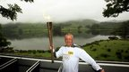 Andrew Holden carries the Olympic flame through Grasmere