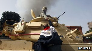 A protester wearing an Egyptian flag reaches to shake hands with a soldier in a tank, Cairo - 29 Jan 2011
