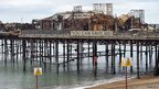 "Hastings pier after fire, with banner saying ""you can save me"""