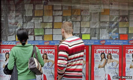 People looking at shop window displaying adverts