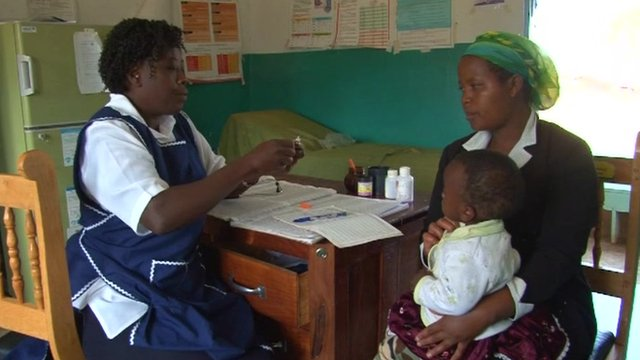 A health worker with a mother and baby