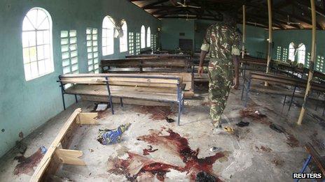 A Kenyan policeman walks inside the a church after an attack in Garissa on 1 July 2012