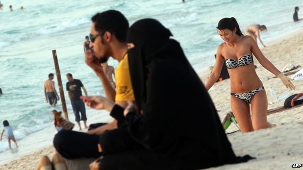 An Emirati couple sit beside the sea on a beach in Dubai