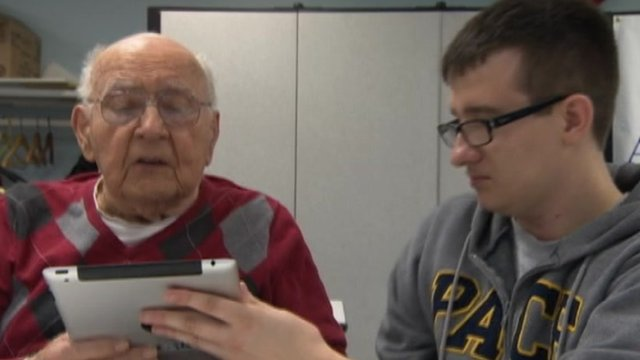 Old and young man looking at tablet