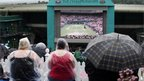 Fans shelter under umbrellas and ponchos on the Hill at the Wimbledon Tennis Championships