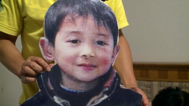 Man holds up cardboard cut-out of his missing son