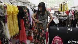 Yi Ling tries on clothes in her hometown