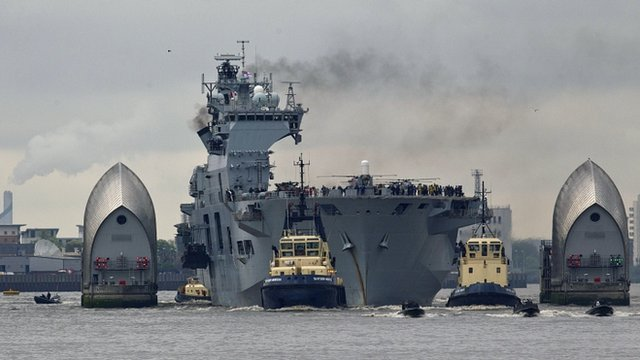 HMS Ocean sails through the Thames Barrier on the River Thames to dock at Greenwich, London