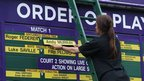 An official makes up the order of play board on the final day at Wimbledon.