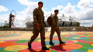 Two soldiers walk past the Olympic stadium in the Olympic Park