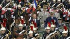 President Francois Hollande, centre, reviews troops in a command car during the Bastille Day military parade on the Champs Elysees in Paris, 14 July 2012.