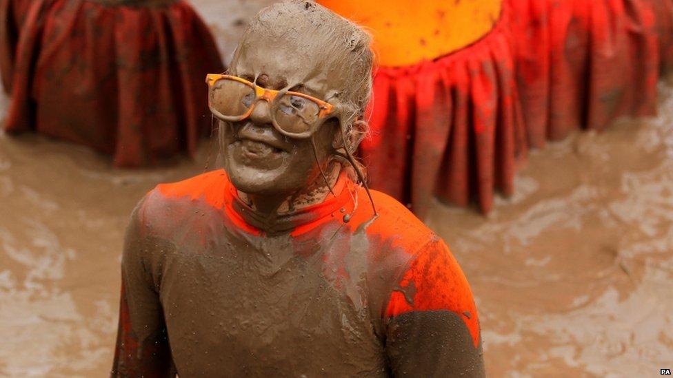 Muddy woman in orange top and orange glasses