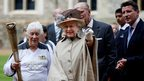The Queen, Prince Philip, Seb Coe and torchbearer Gina Macgregor watch the Olympic flame leave Windsor Castle.