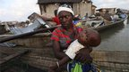 A woman on board a wooden canoe, holding her child, in the Makoko settlement in Lagos, Nigeria.
