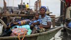 A mother and child on board a boat, with their belongings in tow, on the lagoon of the Makoko settlement