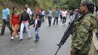 A member of the Revolutionary Armed Forces of Colombia (Farc) watches a group of indigenous people as they walk by an illegal check point at one of Toribio's main access road, in the province of Cauca, 11 July 2012