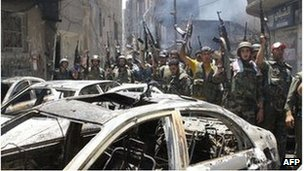 Syrian soldiers celebrate in the Midan area in Damascus on July 20