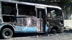 Burnt-out bus seen in the Damascus district of Qabun on 22 July 2012