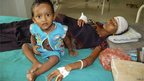 An injured local resident Prnima Das, 32, rests with her child in a hospital after violence near Kokorajhar town in the northeastern Indian state of Assam July 21, 2012.