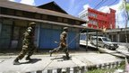 Indian army soldiers run to catch their vehicle during a curfew at Kokrajhar town, in the northeastern Indian state of Assam July 25, 2012