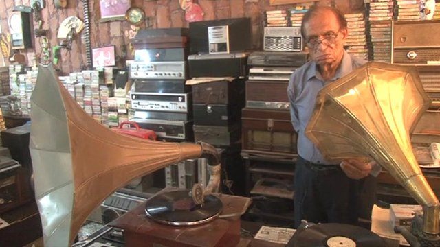 Mian Abdul Quddus standing with two gramophones