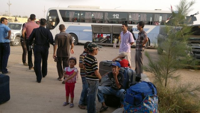 Syrians are seen at the Abu Kamal Iraqi-Syrian border