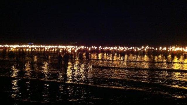 Torchbearers walk into the sea at Weymouth