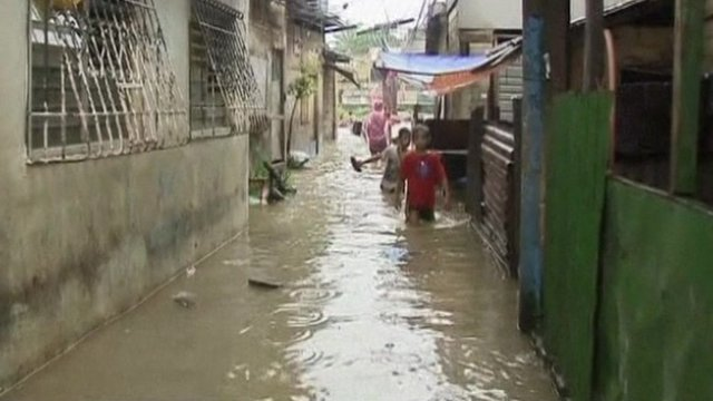 Children walking through waist-deep water on a street