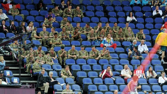 Members of the military sit in unoccupied sponsors seats during the artistic gymnastics team qualification