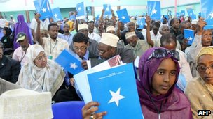 Somali delegates hold up the book of the constitution on July 25, 2012 during the National Constituent Assembly meeting in Mogadishu