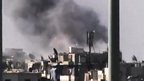 Image from amateur video released by Ugarit News and accessed on 31 July 2012 purports to show black smoke rising from buildings in Aleppo