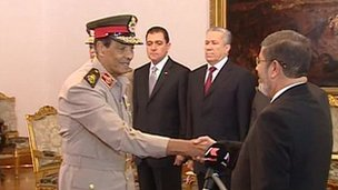Field Marshal Hussein Tantawi shakes hands with Mohammed Mursi