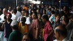 Stranded passengers wait at the New Delhi railway station in Delhi on Monday July 30, 2012