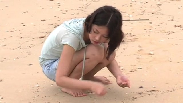 Girl on beach in Hong Kong picking up plastic pellets which had been washed ashore