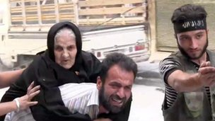 An elderly woman is moved from her home in Aleppo (7 Aug 2012)