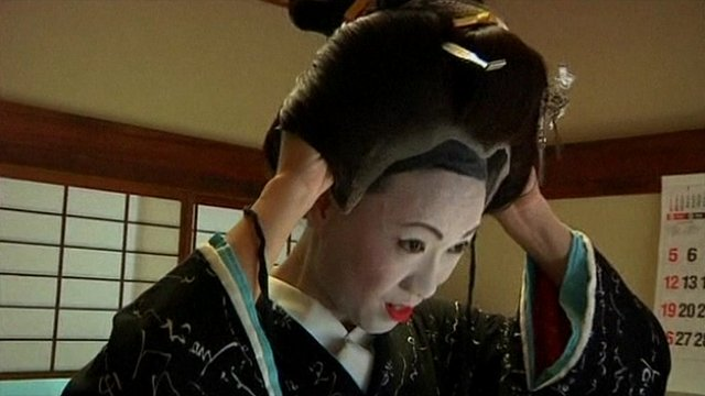 Geisha trainee puts finishing touches to her costume