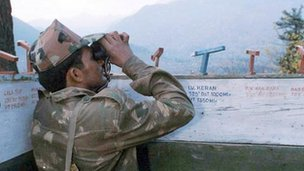 An Indian army soldier monitors Pakistani troop movements with binoculars in a bunker near Keran