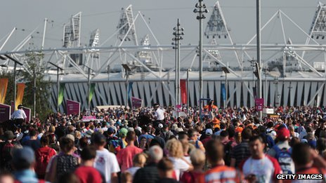 Spectators walk to and from the Olympic stadium