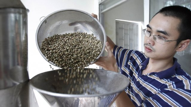 Vu Truong Giang pours coffee beans into a roasting machine at his Giang Lo Duc coffee shop in Hanoi