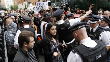 Police officers and protesters supporting Julian Assange