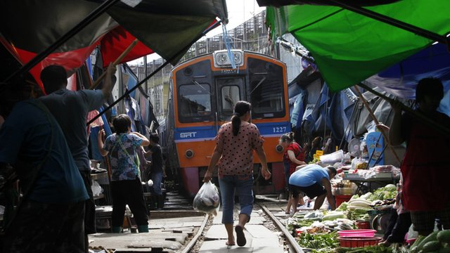 Thai market sellers pull their produce off a railway track to allow a train to pass through in the town of Maeklong