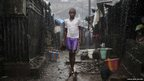 A child stands in pouring rain in the slum of Susan's Bay in Sierra Leone's capital Freetown
