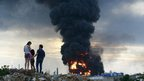 A family observes the fire in the affected area after an explosion at Amuay oil refinery in Punto Fijo in the Peninsula of Paraguana August 25
