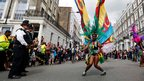 A performer dances in the street during the children's day parade at Notting Hill Carnival in west London