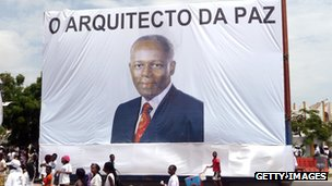 People walk in front of a large portrait of Angola President Jose Eduardo de Santos with text reading 'The Architect of Peace', in the streets of Luanda