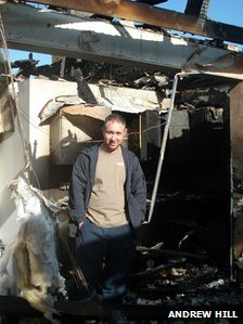 Andrew stands in the wreckage of his bungalow