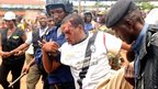 An injured man is carried by police as Guinean opposition protesters were dispersed by police in Conakry - Monday 27 August 2012