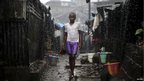 A child stands in the pouring rain in the slum in Sierra Leone - Thursday 23 August 2012