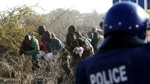 Policeman firing at striking workers at the Marikana platinum mine in South Africa on 16 August 2012 (file pic)
